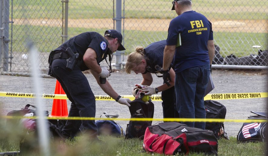 An FBI Evidence Response team inspects the contents of one of the many bags left at the scene of a shooting in Alexandria, Va., Wednesday, June 14, 2017, involving House Majority Whip Steve Scalise of La., and others, during a congressional baseball practice. (AP Photo/Cliff Owen)