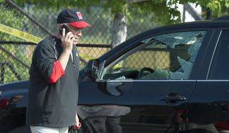 Rep. Brad Wenstrup, R-Ohio, talks on the phone as he walks past a damaged vehicle in Alexandria, Va., Wednesday, June 14, 2017, after a shooting where House Majority Whip Steve Scalise of La., and others, were shot during a congressional baseball practice. (AP Photo/Cliff Owen)