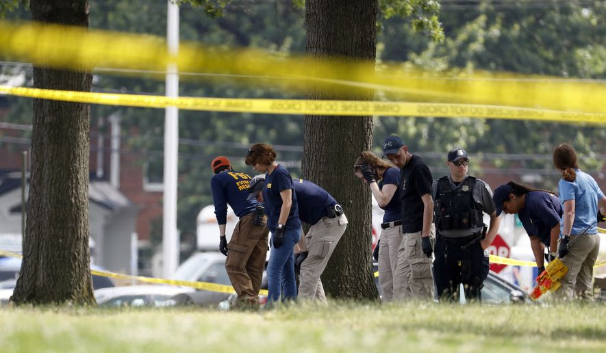 Investigators look for evidence around the baseball field in Alexandria, Va., Wednesday, June 14, 2017, that was the scene of a shooting where House Majority Whip Steve Scalise of La., and others, were shot during a congressional baseball practice. (AP Photo/Alex Brandon)
