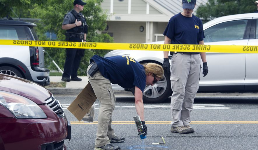 FBI Evidence Response Team members mark evidence at the scene of a multiple shooting in Alexandria, Va., Wednesday, June 14, 2017, where House Majority Whip Steve Scalise of La., and others, were shot at a congressional baseball practice. (AP Photo/Cliff Owen)