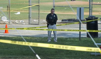 A police office stands watch behind police tape near strewn baseballs on a field in Alexandria, Va., Wednesday, June 14, 2017, after a multiple shooting involving House Majority Whip Steve Scalise of La. (AP Photo/Cliff Owen)