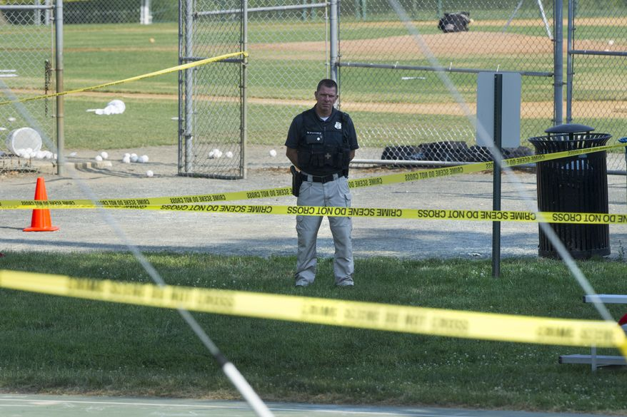 A police office stands watch behind police tape near strewn softballs on a field in Alexandria, Va., Wednesday, June 14, 2017, after a multiple shooting involving House Majority Whip Steve Scalise of La. (AP Photo/Cliff Owen)