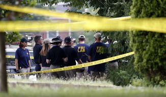Investigators confer before looking for evidence around the baseball field in Alexandria, Va., Wednesday, June 14, 2017, that was the scene of a shooting  involving House Majority Whip Steve Scalise of La., and others, during Congressional baseball practice. (AP Photo/Alex Brandon)