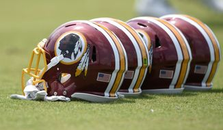 Washington Redskins football helmets sit on the field during an NFL football team practice, Wednesday, June 14, 2017, in Ashburn, Va. (AP Photo/Nick Wass) **FILE**