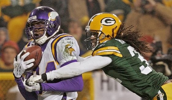 In this Jan. 9, 2005, file photo, Minnesota Vikings receiver Randy Moss catches a 34-yard touchdown pass in front of Green Bay Packers cornerback Al Harris during the fourth quarter of an NFC wild-card playoff football game in Green Bay, Wis. The Vikings will induct Moss into the team's Ring of Honor during the upcoming season. The team also announced on Wednesday, June 14, 2017,  that former receiver Ahmad Rashad will be inducted with Moss in the team's first ceremony since 2013, (AP Photo/Andy Manis, File)