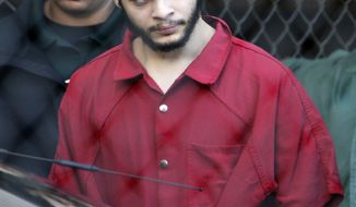 FILE- In this Jan. 30, 2017 file photo, Esteban Santiago is led from the Broward County jail for an arraignment in federal court in Fort Lauderdale, Fla. The Alaska man accused of killing five people at a Florida airport is scheduled for a Wednesday, June 14, 2017, court hearing in Anchorage in an earlier domestic violence case. Santiago had agreed to take part in a deferred sentence program that including completing an anger management course in connection with the 2016 incident. (AP Photo/Lynne Sladky, File)