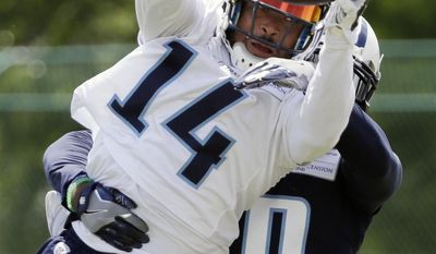 Tennessee Titans wide receiver Eric Weems (14) catches a pass as he is defended by cornerback Demontre Hurst (30) during NFL football minicamp Wednesday, June 14, 2017, in Nashville, Tenn. (AP Photo/Mark Humphrey)