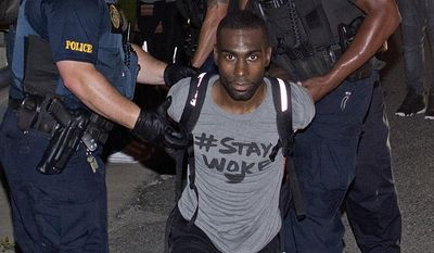 FILE - In this July 9, 2016, file photo, police officers arrest DeRay Mckesson for blocking Airline Highway during a protest in Baton Rouge, La. The activist's attorney claims Black Lives Matter is a movement and not an organization that can be sued by a Louisiana police officer who was injured at a protest after a deadly police shooting.  A federal judge is scheduled to hear arguments Wednesday, June 14, 2017, on whether to dismiss a Baton Rouge police officer's lawsuit against Black Lives Matter and Mckesson, one of nearly 200 protesters arrested after the July 2016 shooting death of Alton Sterling, a black man. (AP Photo/Max Becherer, File)