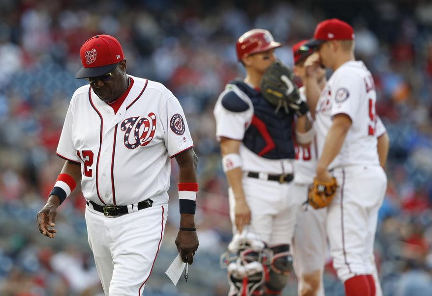 Washington Nationals manager Dusty Baker (12) walks off the field after pulling relief pitcher Blake Treinen and putting in relief pitcher Joe Blanton during the eight inning of a baseball game against the Atlanta Braves at Nationals Park, Wednesday, June 14, 2017, in Washington. The Braves won 13-2. Behind Baker, catcher Jose Lobaton (59) talks with relief pitcher Joe Blanton (56) on the mound.(AP Photo/Carolyn Kaster)