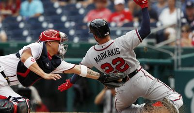Atlanta Braves Nick Markakis (22) slides safe into home off a single hit by teammate Matt Adams as Washington Nationals catcher Jose Lobaton (59) reaches with a late tag during the first inning of a baseball game at Nationals Park, Wednesday, June 14, 2017, in Washington.(AP Photo/Carolyn Kaster)