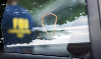 A car window marked as evidence with a marker by an FBI Evidence Response Team member is seen at the scene of a shooting in Alexandria, Va., Wednesday, June 14, 2017, where House Majority Steve Scalise of La., and others, were shot during a congressional baseball practice. (AP Photo/Cliff Owen)