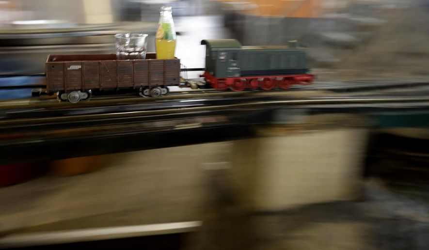 A model freight train carries a beverage to costumers in a restaurant in Prague, Czech Republic, Wednesday, April 19, 2017. In three Czech restaurants, model freight trains arrive at your table and stop right in front of you with your your order of drinks. Petr Fridrich came up with the concept in the Czech city of Brno in 2009. (AP Photo/Petr David Josek)