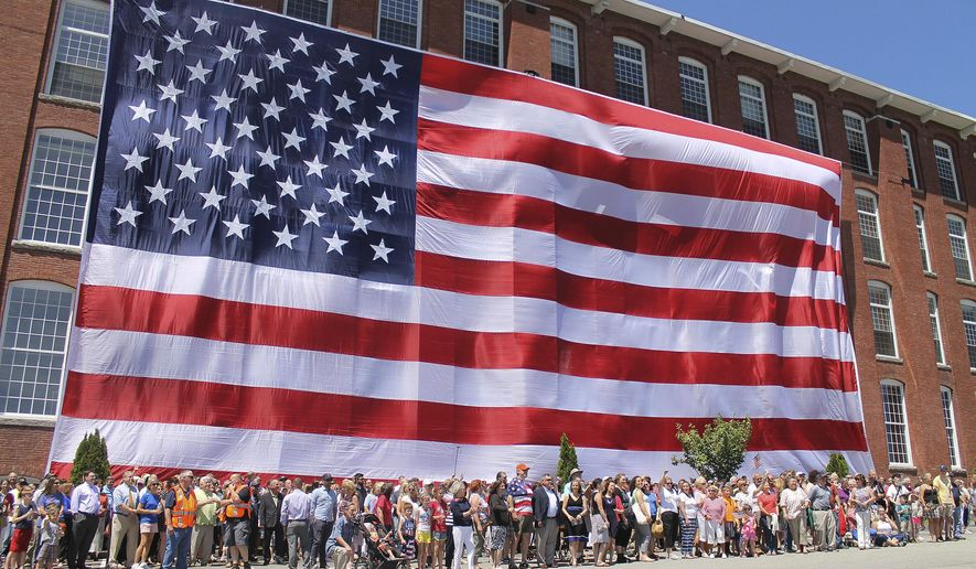"People pose in front of an American flag outside a former textile mill building in Manchester, N.H., on Wednesday, June 14, 2017, to replicate a photo taken in 1914 of workers at the Amoskeag Manufacturing Company with the original ""Great Flag"" they produced. The event was organized by the building's owner, Brady Sullivan Properties, which marked Flag Day by giving donations to the Manchester Historic Association and Liberty House, a veterans organization. (AP Photo/Holly Ramer)"