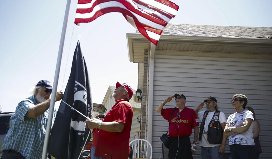 In this Friday June 9, 2017, photo, Mark DeSciscio, left, and Cliff Leach second from left, raise a flag for Tom Miller, center, in Omaha, Neb. With new flagpoles in their yards, disabled veterans in the Omaha area are more than willing to tell their stories of war and sacrifice. (Sarah Hoffman/Omaha World-Herald via AP)