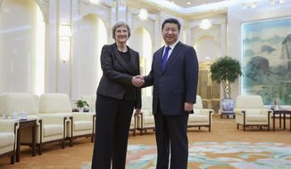In this March 16, 2015, file photo, Chinese President Xi Jinping, right, poses with Harvard University President Drew Faust for photos at the Great Hall of the People in Beijing, China. (AP Photo/Feng Li, Pool, File)