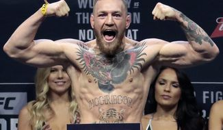 FILE - In this Nov. 11, 2016, file photo, Conor McGregor stands on a scale during the weigh-in event for his fight against Eddie Alvarez in UFC 205 mixed martial arts at Madison Square Garden in New York. Boxer Floyd Mayweather Jr. said Wednesday, June 14, 2017,  he will come out of retirement to face UFC star Conor McGregor in a boxing match on Aug. 26. Mayweather, who retired in September 2015 after winning all 49 of his pro fights, will face a mixed martial arts fighter who has never been in a scheduled 12-round fight at the MGM Grand arena. The fight will take place in a boxing ring and be governed by boxing rules. (AP Photo/Julio Cortez, File)