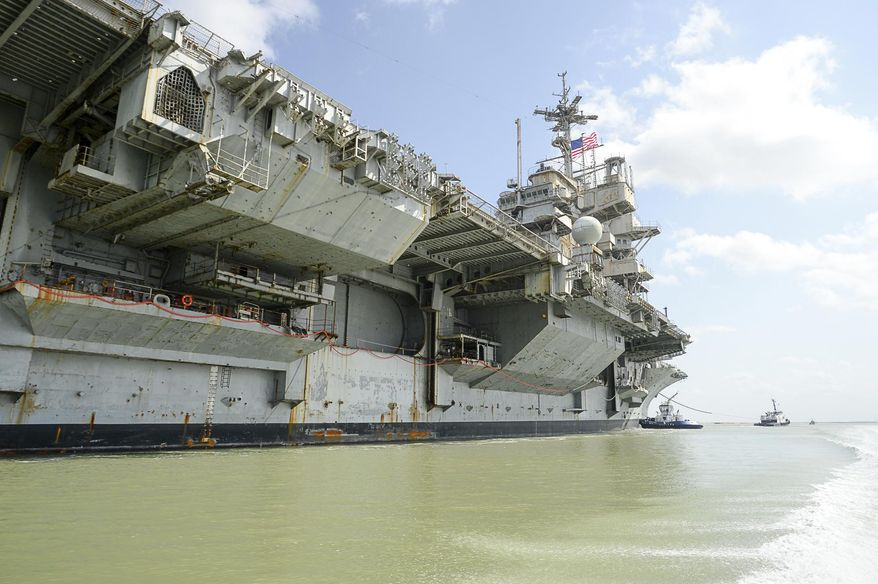 FILE -- In this June 1, 2017, file photo, the decommissioned USS Independence is towed on her final voyage to the Port of Brownsville near Port Isabel, Texas. The Suquamish Tribe and two environmental groups have sued the U.S. Navy, alleging the Navy cleaned the mothballed 60,000-ton USS Independence aircraft carrier in Puget Sound in violation of federal clean-water laws. The ship was cleaned in waters near Bremerton, Wash., in January and February before it was towed to Brownsville, Texas, earlier this month to be dismantled. The tribe, Washington Environmental Council and Puget Soundkeeper Alliance say the Navy scraped the ship's hull and sent toxic copper-based paint, zinc and other pollutants into the water. (Jason Hoekema/The Brownsville Herald via AP, File)