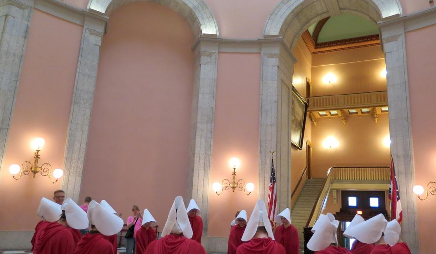 "In this Tuesday, June 13, 2017 photo, women dressed in character from the dystopian novel ""The Handmaid's Tale"" stage a protest in the Ohio Statehouse Rotunda, in Columbus, against a bill criminalizing the state's most common abortion procedure. (Jo Ingles/Ohio Public Radio/TV)"