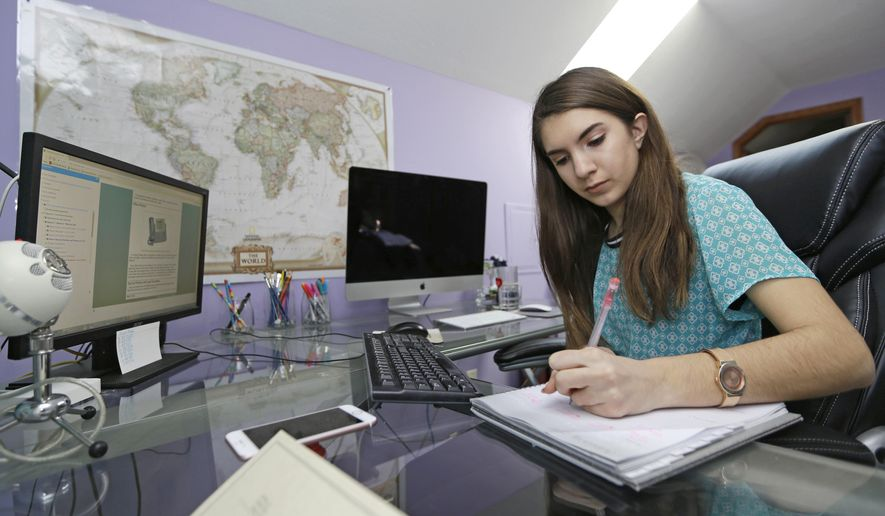 In this Feb. 6, 2017, photo, Celiah Aker, a ninth grader in her fifth year of enrollment in an online charter school named the Electronic Classroom of Tomorrow or ECOT, works on her business and administrative services class at her desk in her home in Medina, Ohio. Members of Ohio's State Board of Education voted Monday, June 12, 2017, to seek repayment of $60 million in funding for the Electronic Classroom of Tomorrow, one of the nation's largest online charter schools, in a dispute over how attendance is tracked. Aker addressed the board members Monday. (AP Photo/Tony Dejak, File)