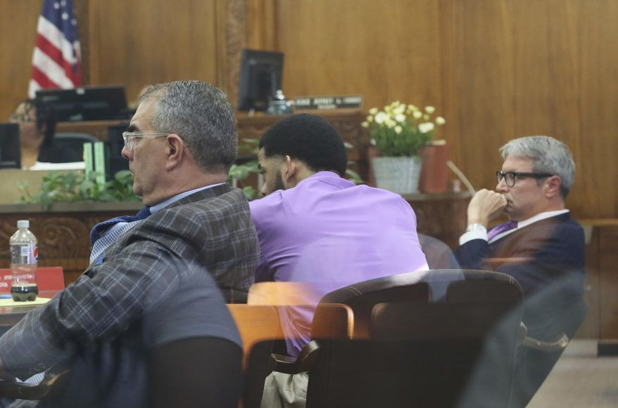 """Dominique Heaggan-Brown, center, with defense attorneys Steven Kohn, left, and Jonathan Smith, appears in court as Milwaukee District Attorney John Chisholm presents his opening statement for the trial of Heaggan-Brown in Milwaukee on Tuesday, June 13, 2017. Chisholm, who charged Heaggan-Brown, a former Milwaukee police officer with killing a black man who fled a traffic stop last year, told a jury Tuesday the man was unarmed and defenseless when the officer shot him """"point blank."""" (Michael Sears/Milwaukee Journal-Sentinel via AP)"""