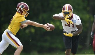 Washington Redskins running back Matt Jones (31) takes a handoff from quarterback Kirk Cousins, left, during an NFL football team practice, Wednesday, June 14, 2017, in Ashburn, Va. (AP Photo/Nick Wass)
