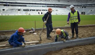 FILE In this file photo taken on Wednesday, Sept. 7, 2016Workers at the Luzhniki stadium, which is undergoing a major rebuild to be ready to host the 2018 World Cup final, in Moscow, Russia. A new report by Human Rights Watch says workers building stadiums for next year's soccer World Cup in Russia have faced repeated abuses and at least 17 have died. The report says workers on several stadiums have routinely gone unpaid for several months. (AP Photo/Ivan Sekretarev, file)