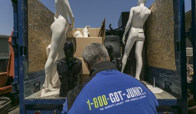 In this Friday, Jun. 9, 2017, photo, 1-800-GOT-JUNK? business owner James Williams loads store mannequins into a truck at his business, in Burbank, Calif. Removing the contents of a store is just one part of the job, says Williams. His company also donates usable equipment like vacuum cleaners to charities and takes furniture and fixtures to businesses that will recycle everything that's usable. (AP Photo/Damian Dovarganes)