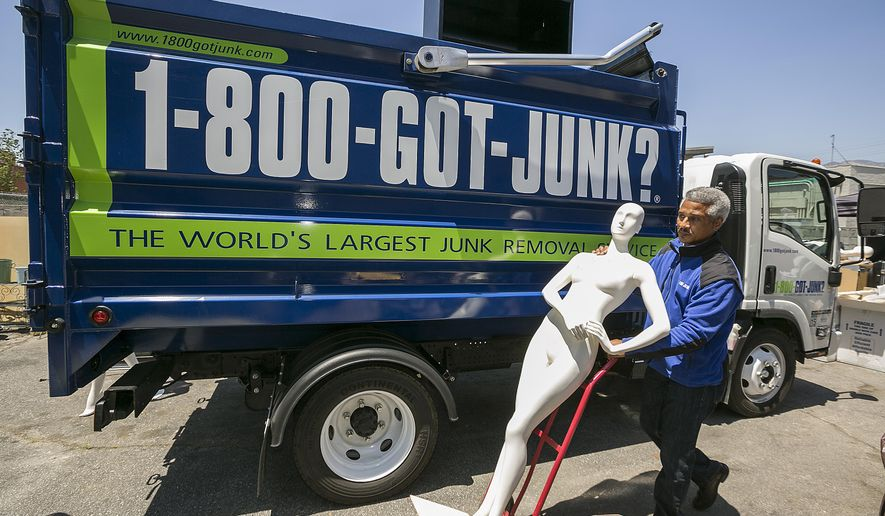 In this Friday, Jun. 9, 2017, photo, 1-800-GOT-JUNK? business owner James Williams gets ready to load a store mannequin into a truck at the business, in Burbank, Calif. Removing the contents of a store is just one part of the job, says Williams. His company also donates usable equipment like vacuum cleaners to charities and takes furniture and fixtures to businesses that will recycle everything that's usable. Williams estimates that he's handled about two store closings a year during the nearly 12 years he's owned the franchise. But there's also a downside for his business when a store closes...he's just lost a customer. (AP Photo/Damian Dovarganes)