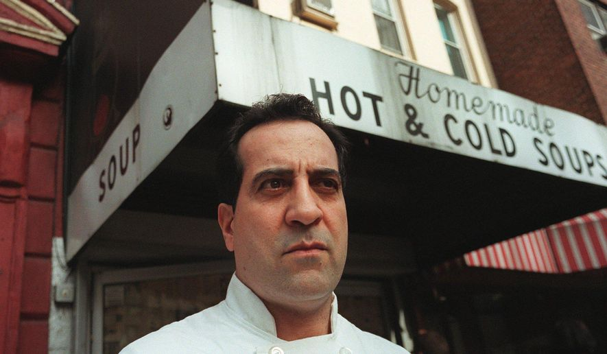 """FILE - In this 1997 file photo, Al Yeganeh poses for a photograph outside his business, Soup Kitchen International, in New York. The company that sells soup made with Yeganeh's recipes has filed for bankruptcy less than a month after its chief financial officer was arrested on charges of cheating the government out of employment-related taxes. Yeganeh was the inspiration for the """"Soup Nazi"""" character on """"Seinfeld"""" (AP Photo/Michael Schmelling, File)"""