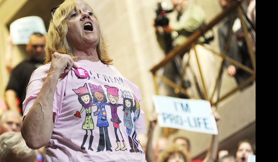 """A woman interrupts a speaker to voice her support for Pro Choice during the Pro Life rally at the Missouri State Capitol in Jefferson City, Mo., Wednesday, June 14, 2017. The crowd responded back by chanting, """"We are Pro Life,"""" as the woman was escorted out by security. (Mikala Compton/The Jefferson City News-Tribune via AP)"""