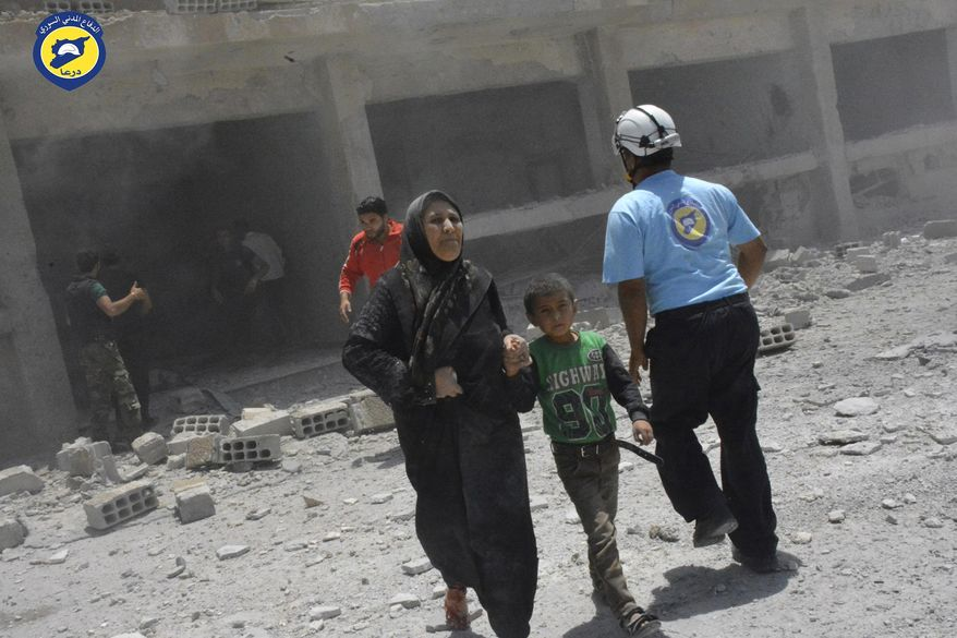 "This photo provided by the Syrian Civil Defense group known as the White Helmets, shows civilians rushing out of the damaged buildings after airstrikes hit a school housing a number of displaced people,  in the western part of the southern Daraa province of Syria, Wednesday, June 14, 2017. A U.N. investigative commission said Wednesday the ""de-escalation"" agreement in Syria has reduced violence in only one of four zones included in the deal and has not led to greater humanitarian access. (Syrian Civil Defense White Helmets via AP)"