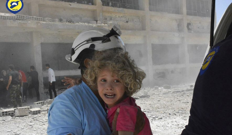 """This photo provided by the Syrian Civil Defense group known as the White Helmets, shows a civil defense worker carrying a child after airstrikes hit a school housing a number of displaced people, in the western part of the southern Daraa province of Syria, Wednesday, June 14, 2017. A U.N. investigative commission said Wednesday that the """"de-escalation"""" agreement in Syria has reduced violence in only one of four zones included in the deal and has not led to greater humanitarian access. (Syrian Civil Defense White Helmets via AP)"""
