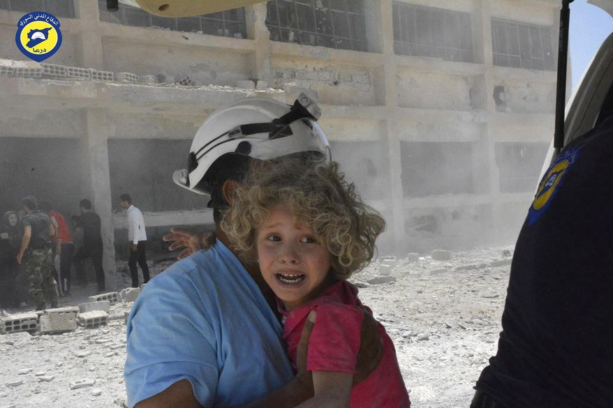 "This photo provided by the Syrian Civil Defense group known as the White Helmets, shows a civil defense worker carrying a child after airstrikes hit a school housing a number of displaced people, in the western part of the southern Daraa province of Syria, Wednesday, June 14, 2017. A U.N. investigative commission said Wednesday that the ""de-escalation"" agreement in Syria has reduced violence in only one of four zones included in the deal and has not led to greater humanitarian access. (Syrian Civil Defense White Helmets via AP)"