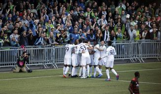 Seattle Sounders players surround midfielder Zach Mathers and celebrate in front of fans after Mathers scored a goal against the Portland Timbers during the second half of a U.S. Open Cup soccer match, Tuesday, June 13, 2017, in Tukwila, Wash. The Sounders won 2-1. (AP Photo/Ted S. Warren)
