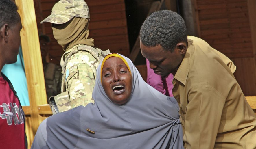"""A mother whose daughter was shot in the head by attackers during a militant attack on a restaurant, grieves in Mogadishu, Somalia Thursday, June 15, 2017. Somalia's security forces early Thursday morning ended a night-long siege by al-Shabab Islamic extremists at the popular """"Pizza House"""" restaurant in the capital. (AP Photo/Farah Abdi Warsameh)"""
