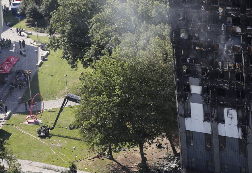 Britain's Prime Minister Theresa May, in group left, arrives at Grenfield Tower, right, in London, Thursday, June 15, 2017, following a deadly fire in the apartment block.  A massive fire raced through the 24-storey high-rise apartment building in west London early Wednesday, and London fire commissioner says it will take weeks for the building to be searched and 'cleared'.(AP Photo/Frank Augstein)