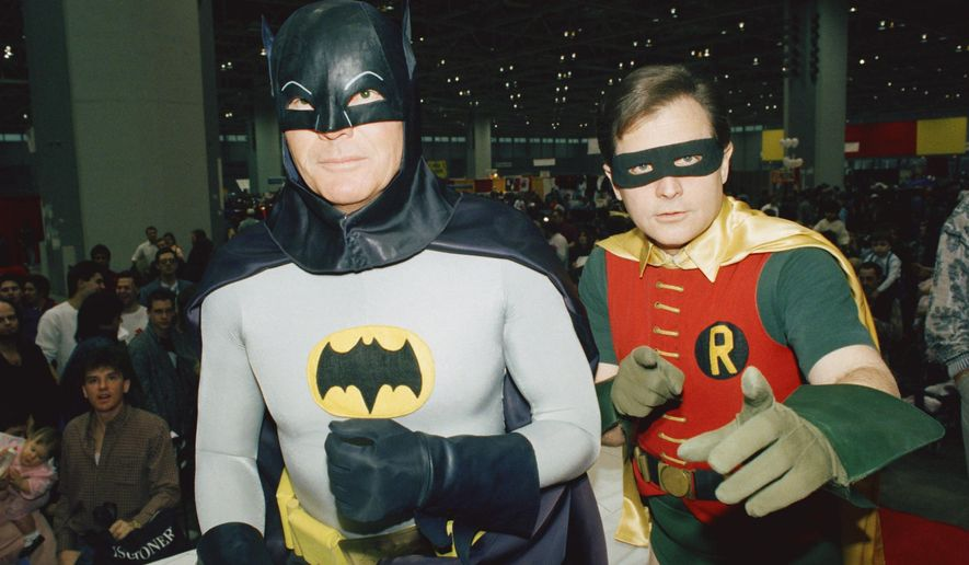 "FILE - In this Jan. 27, 1989, file photo, actors Adam West, left, and Burt Ward, dressed as their characters Batman and Robin, pose for a photo at the ""World of Wheels"" custom car show in Chicago. Los Angeles Mayor Eric Garcetti says the Bat-Signal will shine over the city on Thursday, June 15, 2017 in tribute to West, who died June 9 at the age of 88. (AP Photo/Mark Elias, File)"