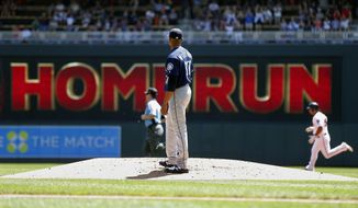 Seattle Mariners pitcher Ariel Miranda looks back after he gave up a two-run home run to Minnesota Twins' Eduardo Escobar, right, in the first inning of a baseball game Thursday, June 15, 2017, in Minneapolis. (AP Photo/Jim Mone)