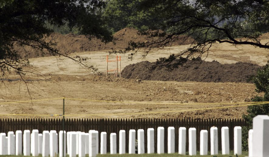File-This June 17, 2005, file photo shows tombstones at Arlington National Cemetery in front of land under preparation for cemetery expansion in Arlington, Va. Arlington National Cemetery is moving ahead with plans to expand by roughly 50,000 spaces, extending the cemetery's life beyond 2050. The cemetery is run by the Army. For several years, military officials tried to negotiate a land swap with Arlington County that would allow the cemetery to expand and accommodate the county's needs as well. (AP Photo/J. Scott Applewhite, File)