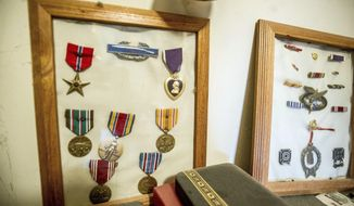 ADVANCE FOR USE ON SATURDAY, JUNE 17- In this Thursday, June 8, 2017, photograph, two display cases hold the medals earned by John Tripp, a veteran of World War II who served in the famed 10th Mountain Division, in his home in Carbondale, Colo. (Anna Stonehouse/The Aspen Times via AP)