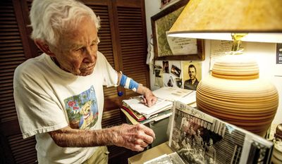 ADVANCE FOR USE ON SATURDAY, JUNE 17-In this Thursday, June 8, 2017, photograph, John Tripp, a veteran of World War II who served in the famed 10th Mountain Division, looks over some memorabilia from his years in the military in his home in Carbondale, Colo. (Anna Stonehouse/The Aspen Times via AP)