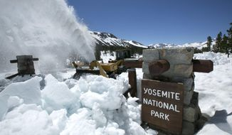 In this photo taken Tuesday, June 6, 2017, a National Park Service snow blower clears the entrance to Yosemite National Park, Calif. This year's heavy snowfall has crews working to clear Highway 120 as summer approaches, the only road through Yosemite that connects the Central Valley on the west side with the Owens Valley on the east side of the Sierra Nevada. Crews used plows, excavators, and massive snow blowers to open the eastern entrance to Yosemite. (AP Photo/Rich Pedroncelli)