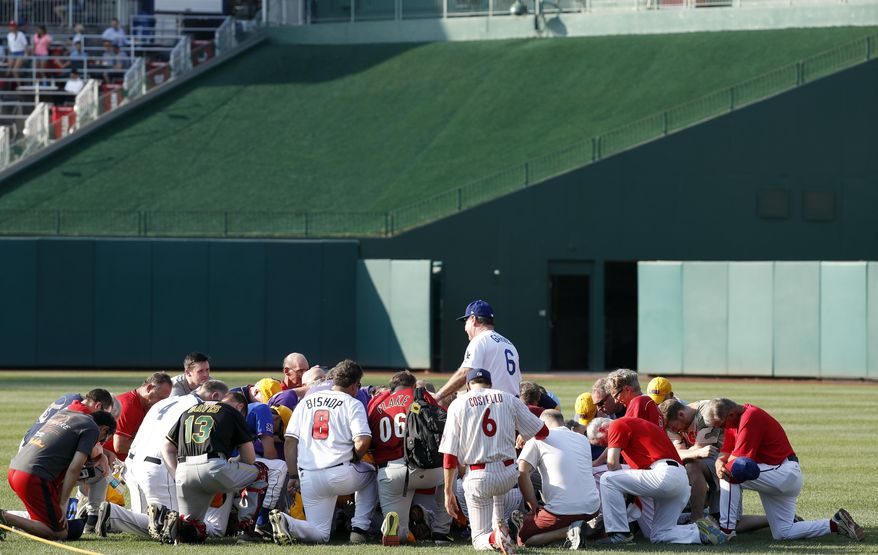Steve Garvey, former Los Angeles Dodgers player, leads a prayer for the Republican team before the Congressional baseball game, Thursday, June 15, 2017, in Washington. The annual GOP-Democrats baseball game raises money for charity. (AP Photo/Alex Brandon)