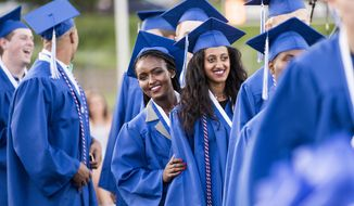 ADVANCE FOR SATURDAY, JUNE 17, 2017 AND THEREAFTER - In this Wednesday, June 7, 2017, photo, Jerusalem Dregne, left, and Frehiwot Dregne, right, stand in line to receive their diplomas during the Janesville Craig High School graduation ceremony at Monterey Stadium in Janesville, Wis. The girls were adopted by Dennis and Connie from Ethiopia. (Angela Major/The Janesville Gazette via AP)