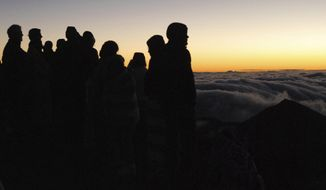 FILE - In this Jan. 22, 2017, file photo, people gather ahead of the sunrise on the summit of Haleakala volcano in Haleakala National Park on Hawaii's island of Maui. The National Park Service is studying whether to keep its new system requiring reservations to drive up to Haleakala's summit to see the sunrise. The agency said Thursday, June 15  it will conduct an environmental assessment for the program, which was implemented on an emergency basis earlier this year to address overcrowding. (AP Photo/Caleb Jones, File)