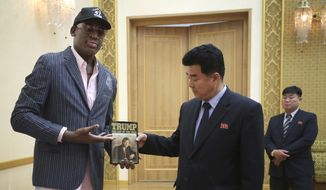 "Former NBA basketball star Dennis Rodman presents a book titled ""Trump The Art of the Deal"" to North Korea's Sports Minister Kim Il-guk Thursday, June 15, 2017, in Pyongyang, North Korea. (AP Photo/Kim Kwang Hyon)"