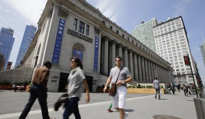 Pedestrians pass a new entrance to the West End Concourse at the Farley Post Office building Thursday, June 15, 2017, in New York. The entrance is part of the first phase of the redevelopment of the historic post office, and initially was scheduled to be opened last year. (AP Photo/Frank Franklin II)
