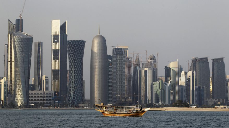 FILE - In this Thursday Jan. 6, 2011 file photo, a traditional dhow floats in the Corniche Bay of Doha, Qatar, with tall buildings of the financial district in the background. Qatar says it has pulled all of its troops from the border of Djibouti and Eritrea, East African nations that have a long-running territorial dispute which Doha had helped mediate. (AP Photo/Saurabh Das, File)