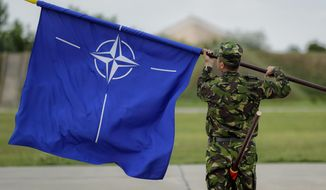 "A Romanian serviceman furls the NATO flag after Britain's Defense Minister Michael Fallon's visit at the Mihail Kogalniceanu air base in Romania, Wednesday, June 14, 2017.  Britain's defense minister praised Romanian and British pilots for protecting the Black Sea region from ""the persistent threat of Russian aggression,"" saying that Britain remains committed to NATO and the European security.(AP Photo/Vadim Ghirda)"