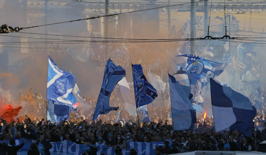 FILE - In this Saturday, April 28, 2012 file photo Zenit's fans march prior the match of their team in the national soccer Championship in downtown St.Petersburg, Russia. A new report seen by the Associated Press shows Russia has made progress fighting football racism ahead of the Confederations Cup and next year's World Cup, but warns that anti-Semitism in stadiums has grown and that racist fans are using far-right codes to smuggle offensive messages into stadiums. (AP Photo/Dmitry Lovetsky, File)